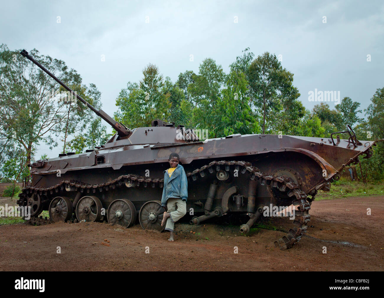 Boy In Front Of A Tank Wreck From Civil War, Bie Area, Angola - Stock Image