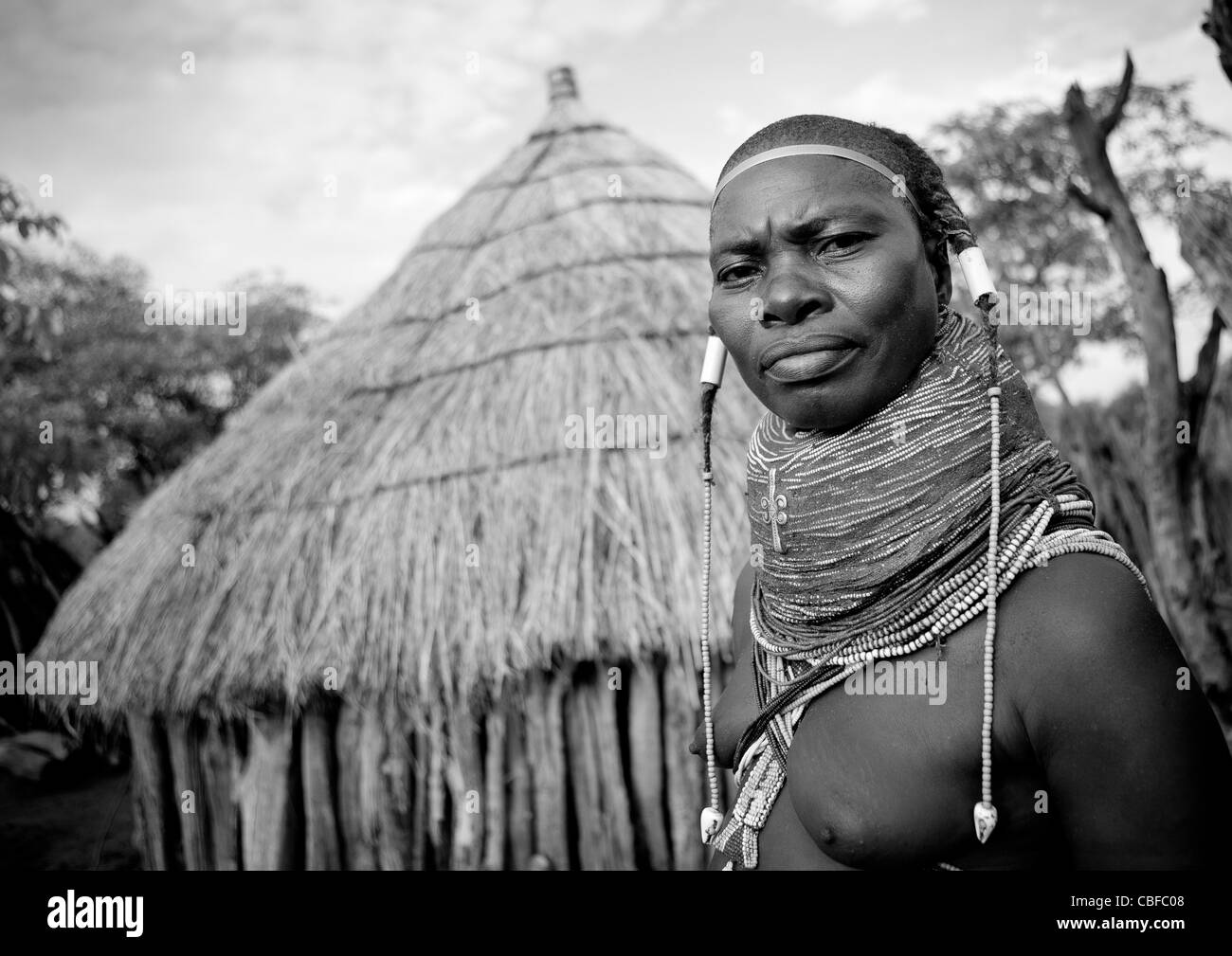 Mwila Woman With A Vilanda Necklace In Front Of Her Hut, Chibia Area, Angola - Stock Image