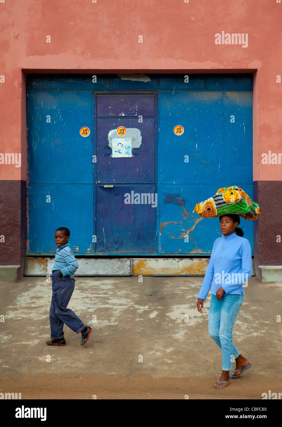Boy And Woman Carrying A Load On Her Head In Lubango Streets, Angola - Stock Image