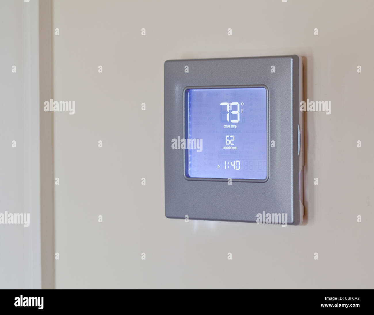 Electronic thermostat with blue LCD screen for controlling air conditioning and heating HVAC - Stock Image