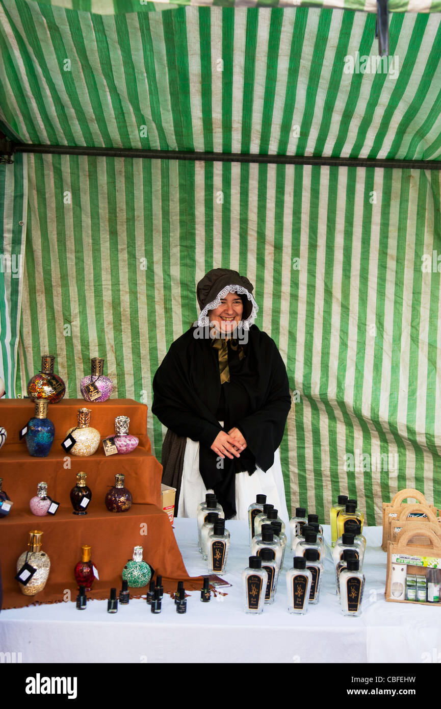 Louth Victorian Market,  Lincolnshire, England lady selling potions and lotions to cure ailments wearing bonnet - Stock Image
