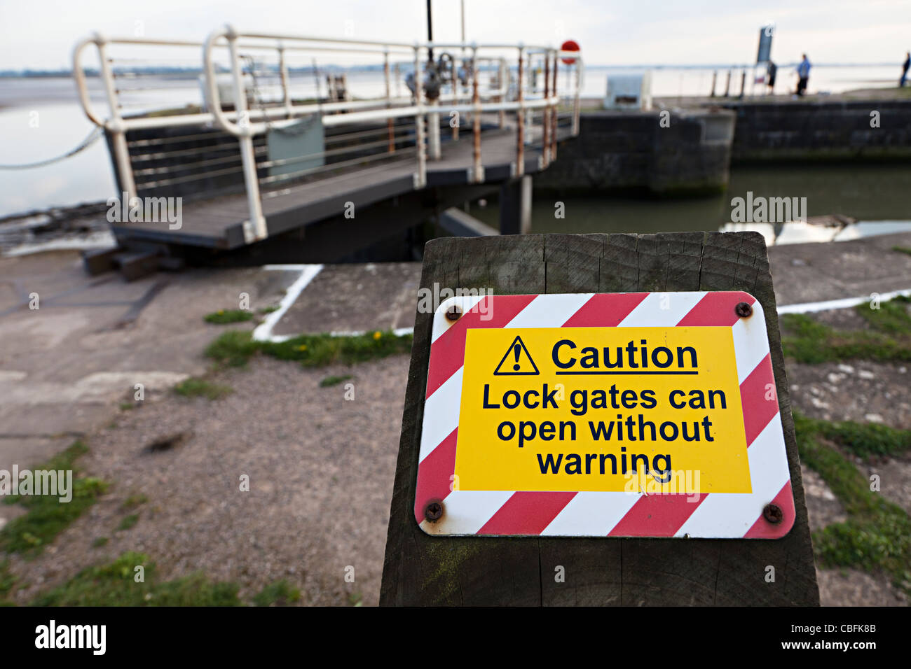 Caution lock gates can open without warning sign Lydney harbour regeneration project River Severn England UK - Stock Image