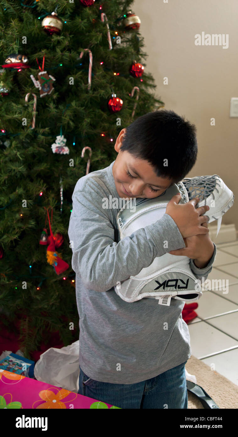 interracialHispanic American boy receives his dream gift of a goal tenders goaly hockey glove Christmas.present - Stock Image