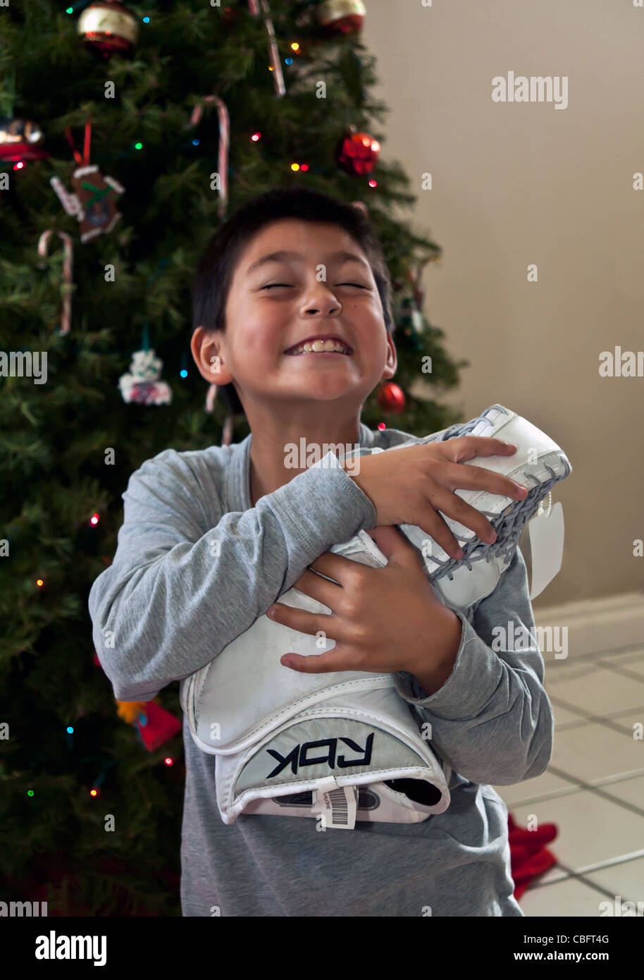 interracial multicultural Hispanic American child receives his gift goal tenders goaly hockey glove Christmas.present - Stock Image