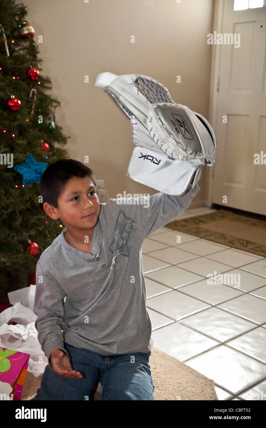 9-10 year old Hispanic American boy receives his dream gift of a goal tenders goaly hockey glove Christmas.present - Stock Image