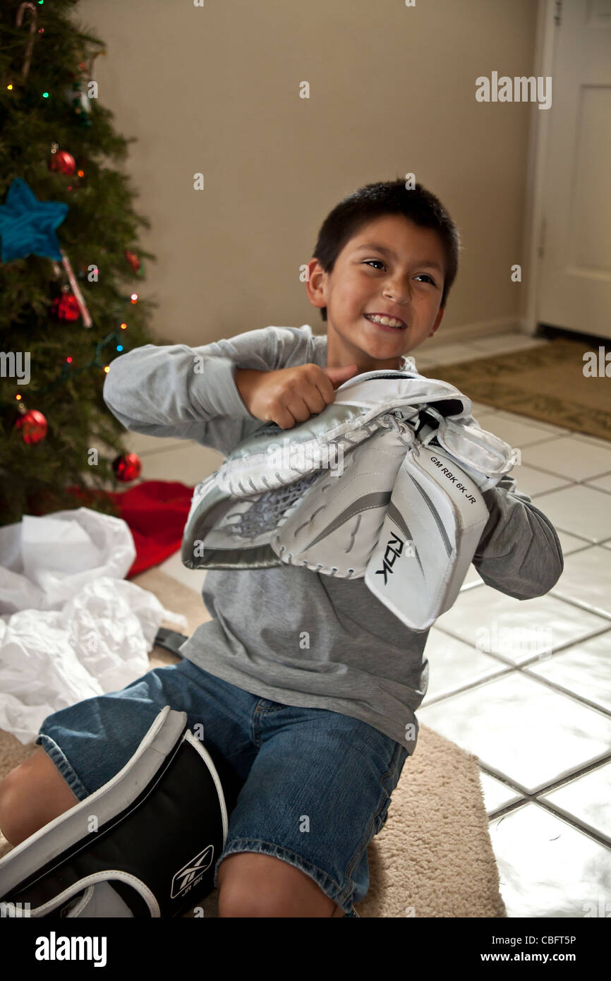 Hispanic interracial multiculyural boy receives his dream gift of a goal tenders goaly hockey glove Christmas.present - Stock Image