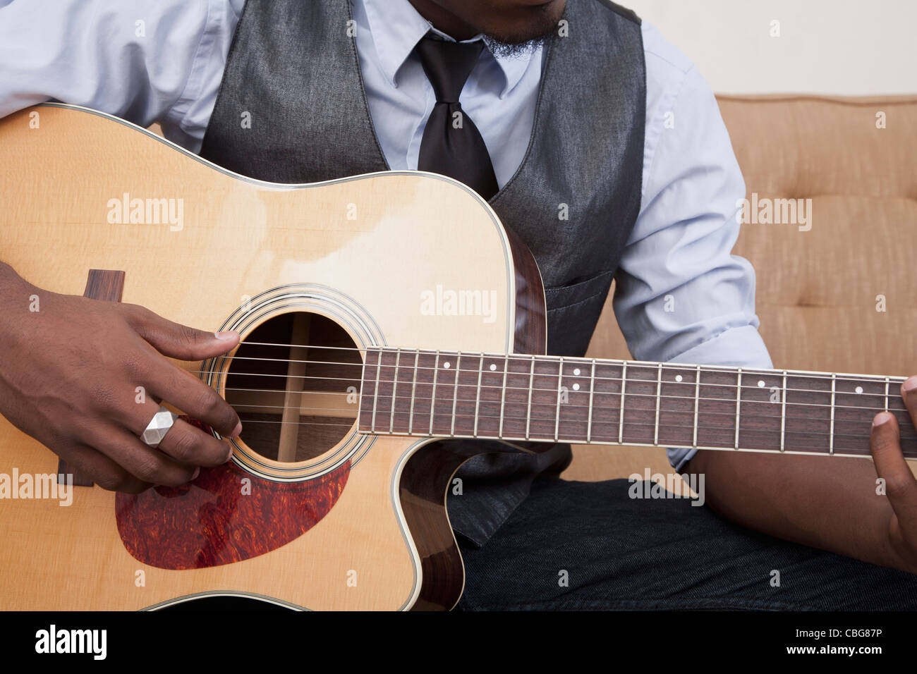 A young man playing an acoustic guitar, focus on midsection - Stock Photo