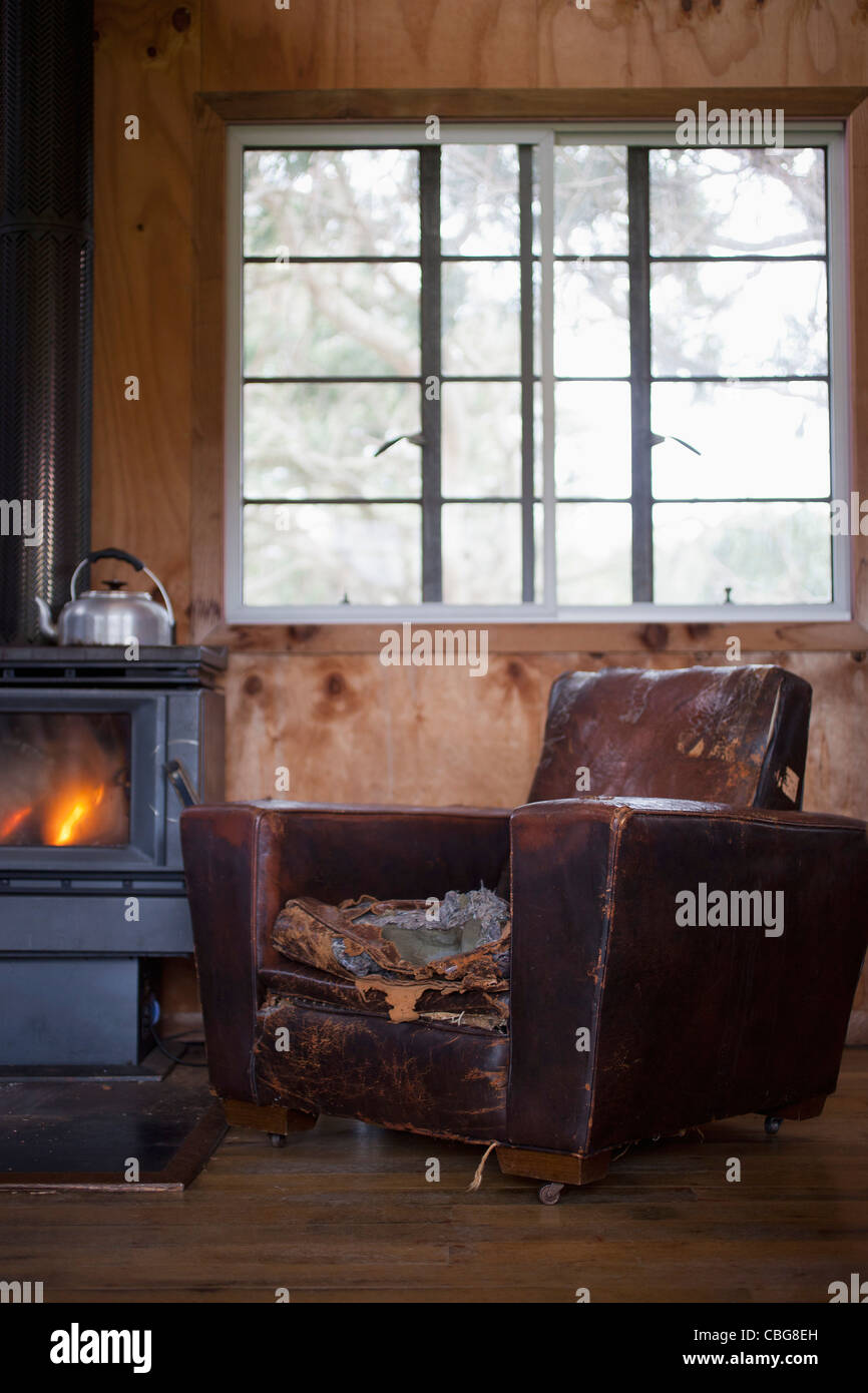A well worn leather armchair next to a wood burning stove - Stock Image