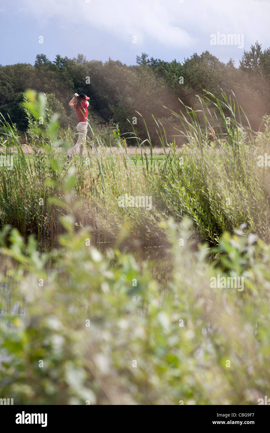 A female golfer teeing off, focus on background - Stock Image