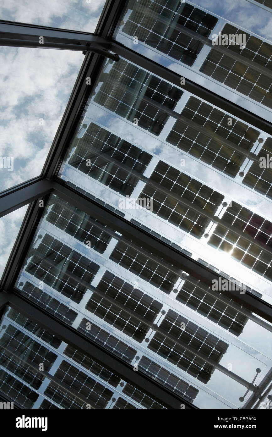 Under a row of solar panels on an open roof with sky in background - Stock Image