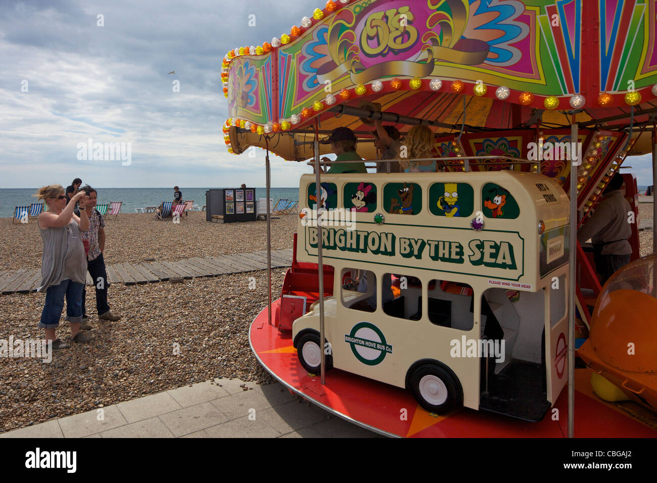 Children's roundabout on the seafront at Brighton beach, West Sussex, England, UK, United Kingdom, GB, Great - Stock Image