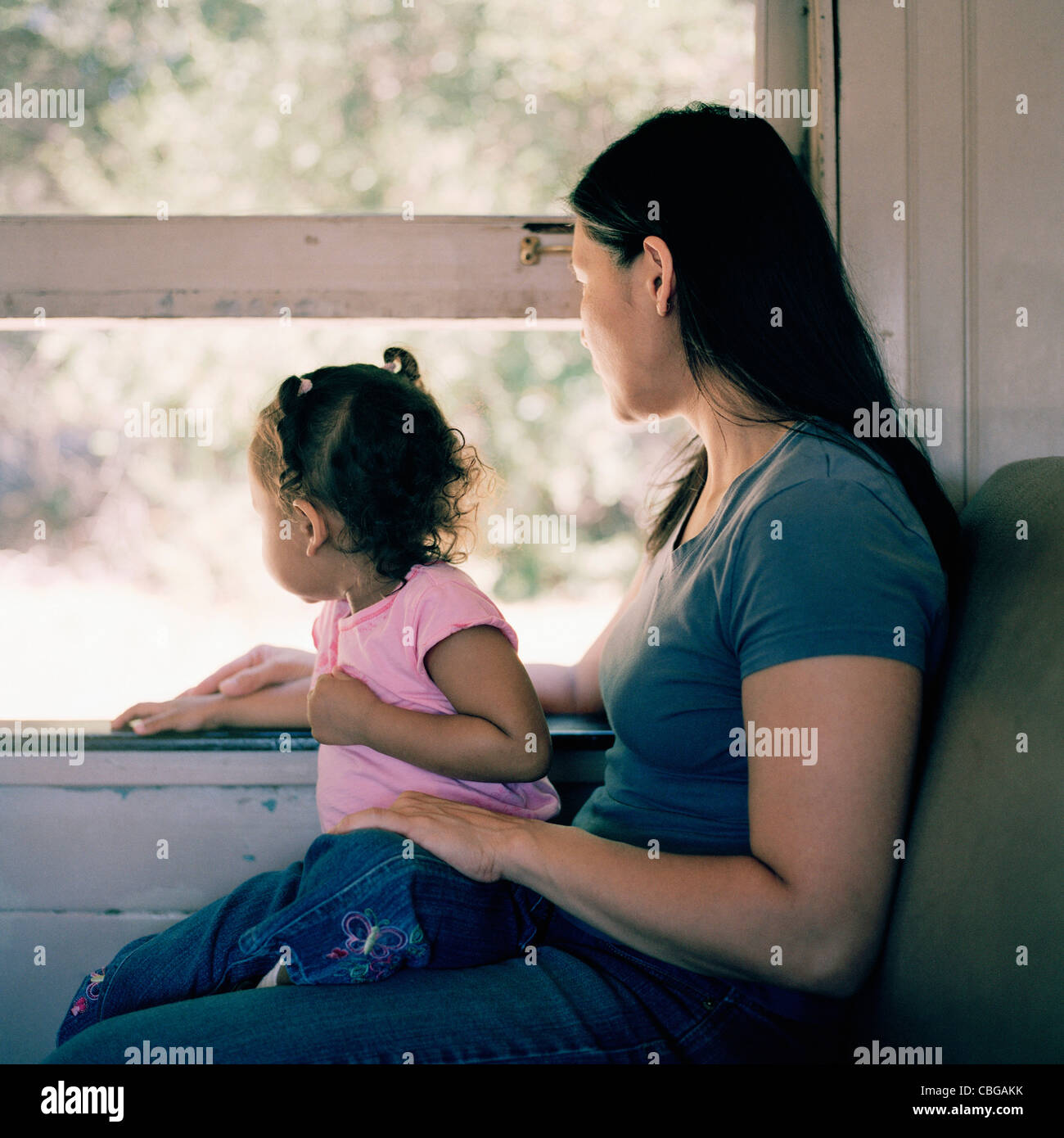 A mother and daughter on a train, looking through window - Stock Image