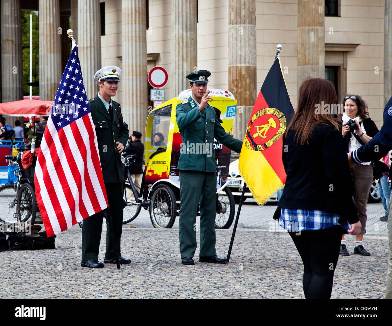 Actors dressed in American and East German military uniform posing for tourists in front of Brandenburg Gate, Berlin, - Stock Image