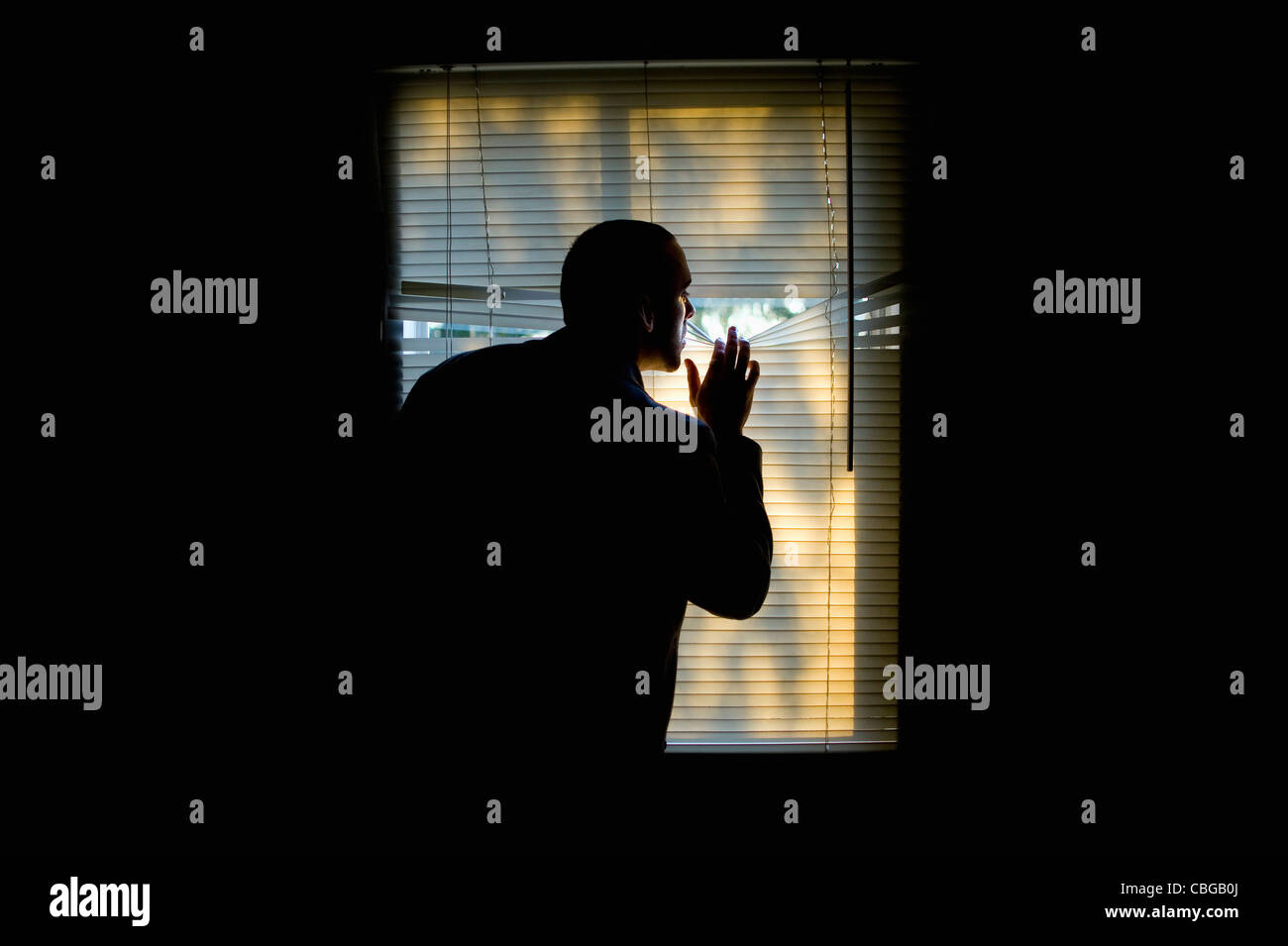 A man peeking outdoors through the blinds of a darkened room - Stock Image