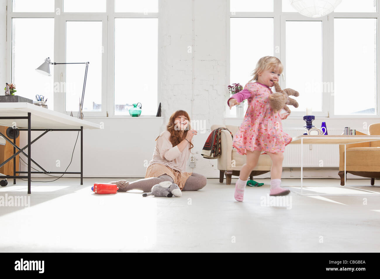 A young girl carrying a stuffed toy in her mouth running around Stock Photo