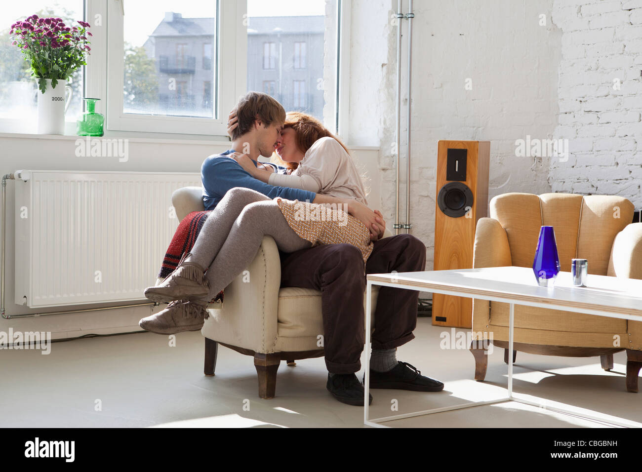 A young woman sitting on her boyfriend's lap, kissing - Stock Image