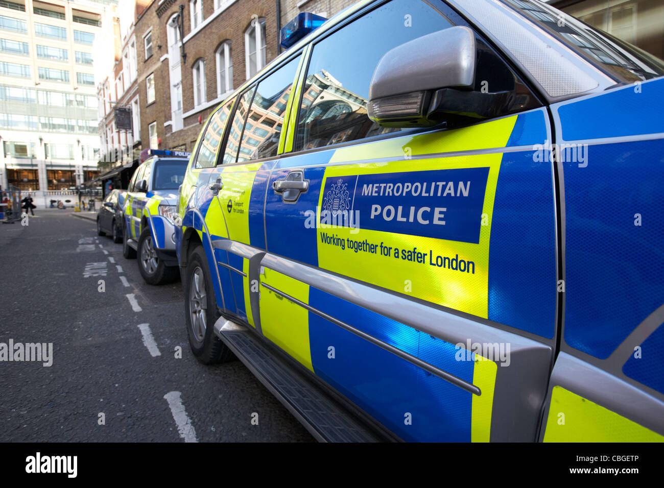 metropolitan police vehicles with battenburg chequered livery parked in reserved onstreet bays london england uk - Stock Image