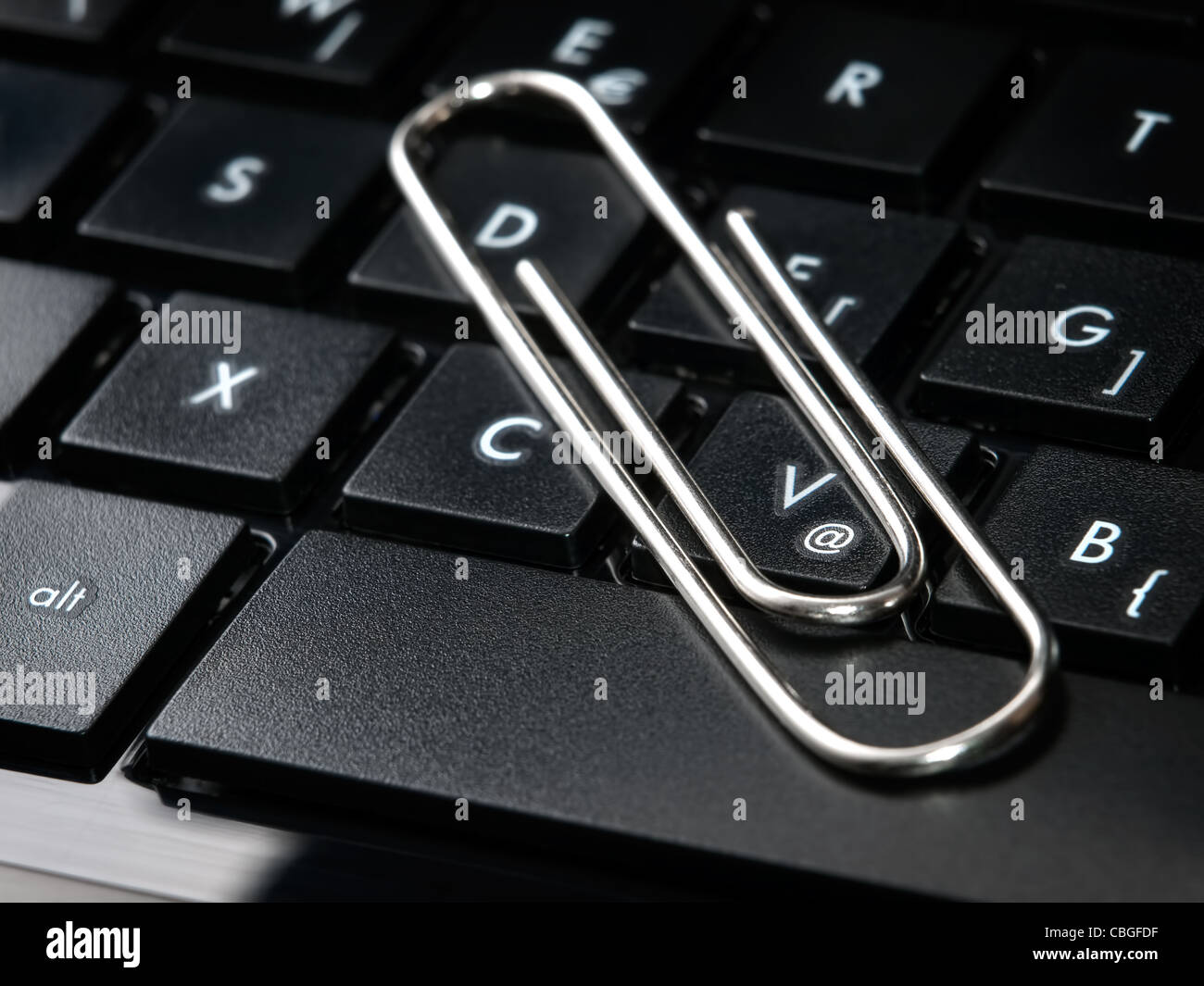 Paper clip on the keyboard as a metaphor about sending an attachment in e-mails. - Stock Image