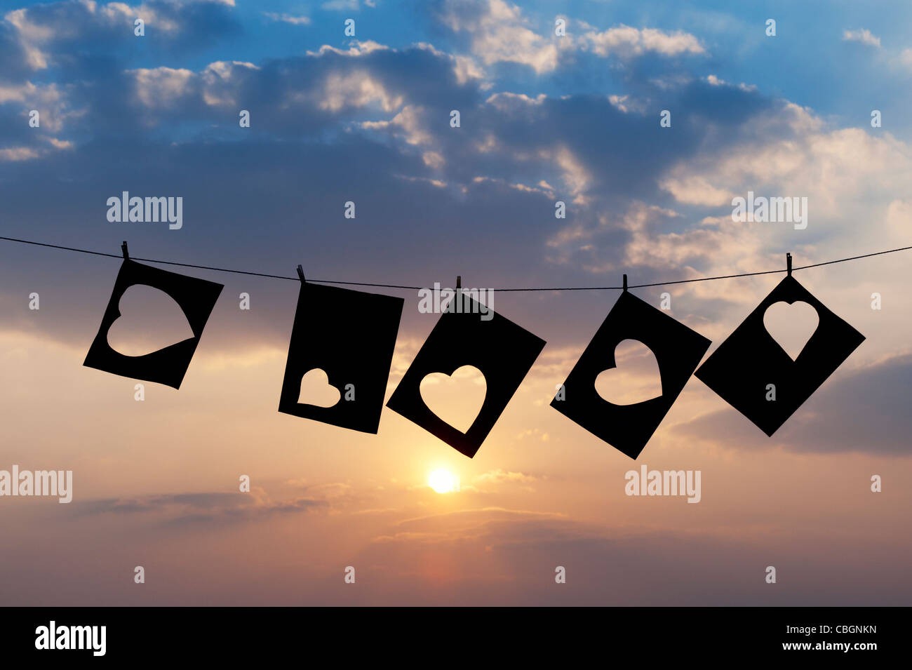 Cut out heart shapes hanging on a line against sunset. Silhouette - Stock Image