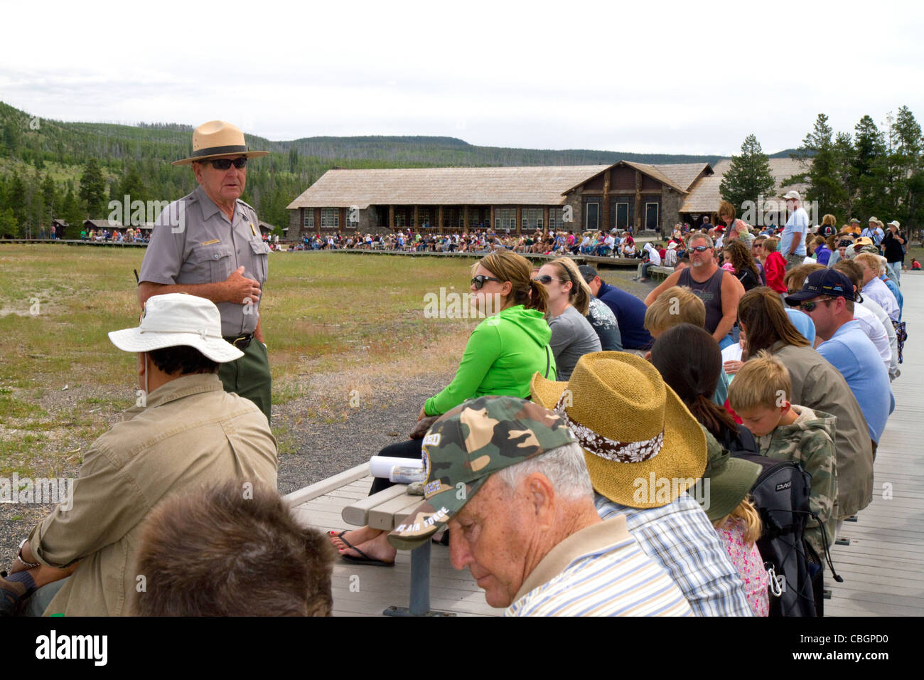 Park ranger giving a tour group information about Old Faithful geyser in Yellowstone National Park, Wyoming, USA. - Stock Image