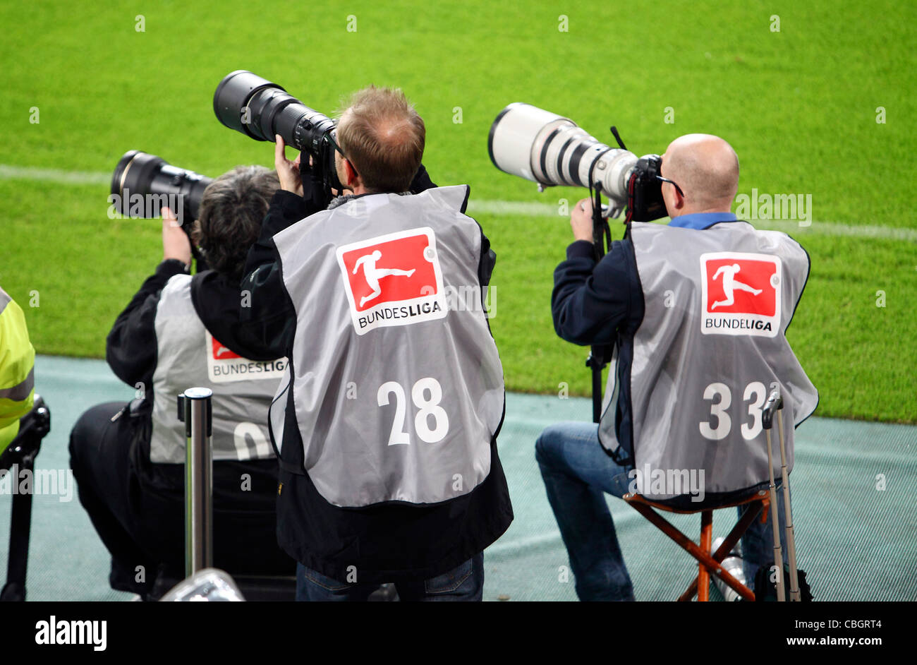 Press photographers during a football game in a sports stadium, with long telephoto lenses. - Stock Image