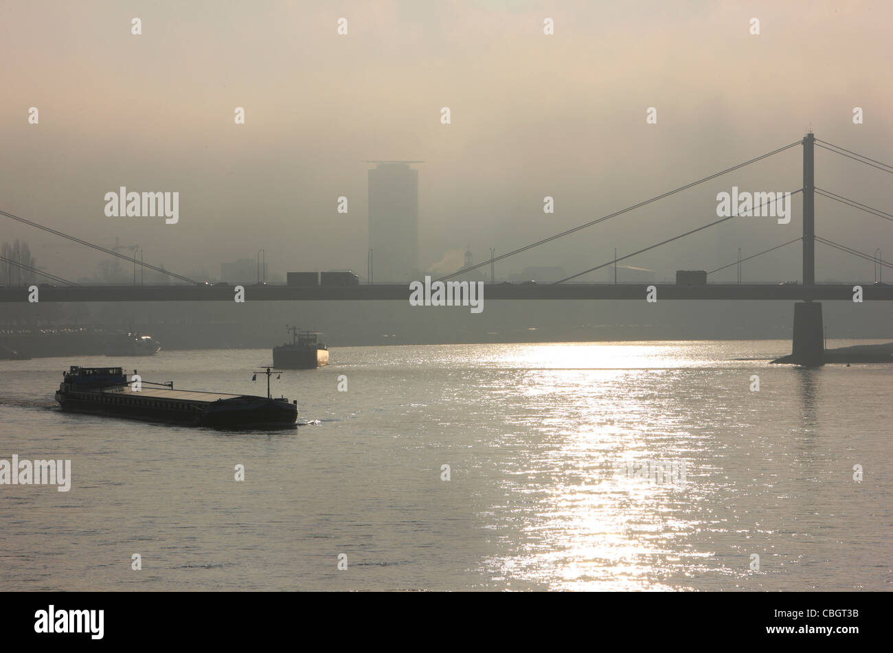 River Rhine in fall, autumn, foggy day. Freight ships passing a bridge in Düsseldorf, Germany. - Stock Image
