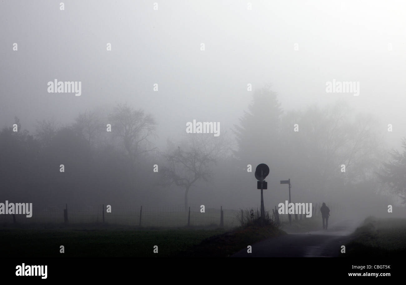 Autumn, fog, countryside, person walking on a path in thick fog. Essen, Germany. Stock Photo