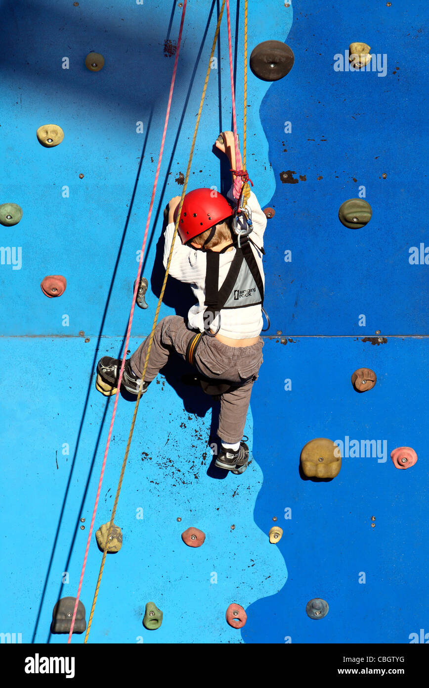 Young boy at a climbing wall. - Stock Image
