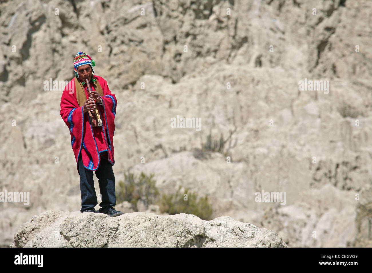 Traditional dressed native Indian flute player with poncho in the Valley of the Moon / Valle de la Luna near La - Stock Image