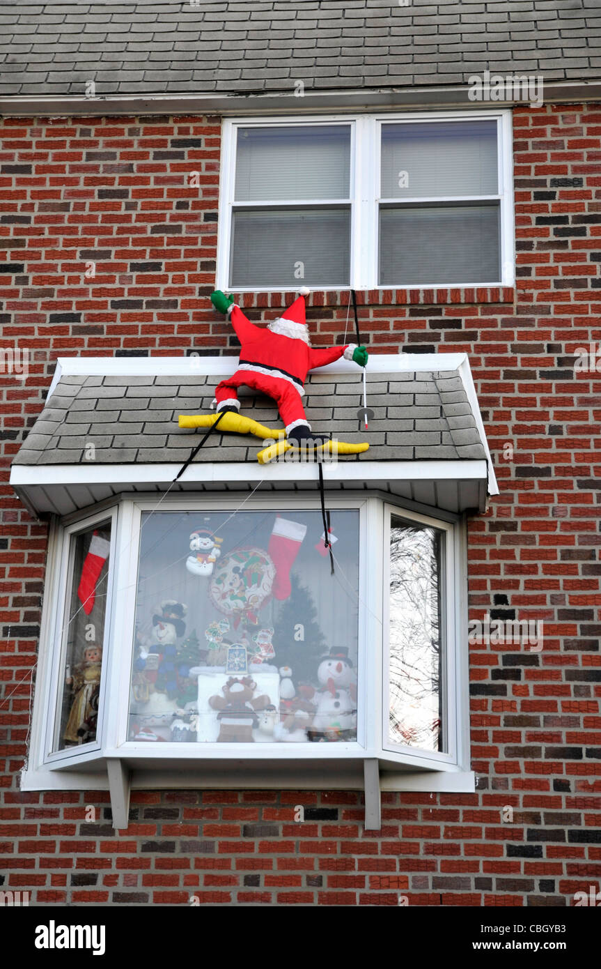 Santa Claus climb to  window with Christmas gifts for kids - Stock Image