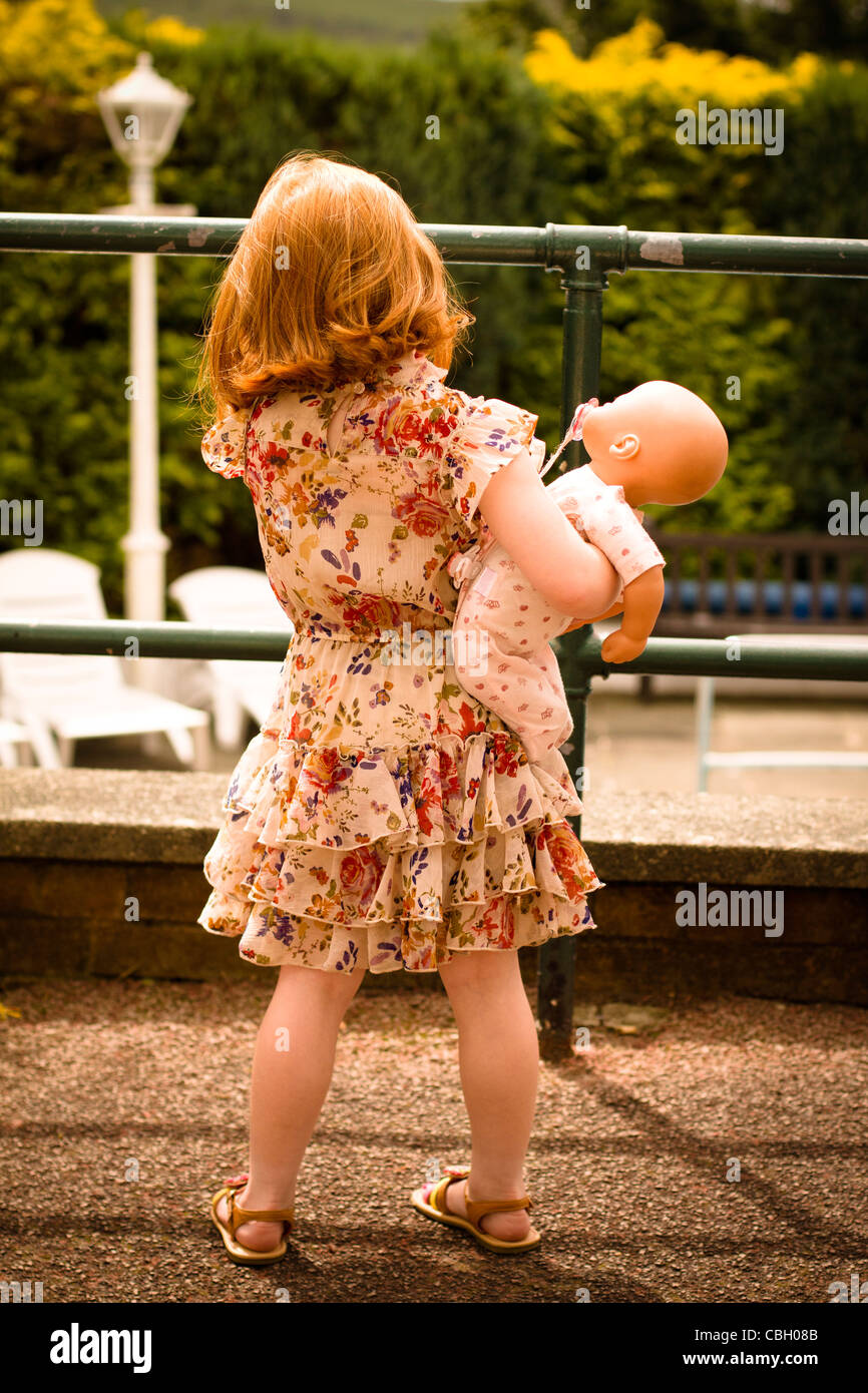 Rear of a little girl, aged 5, holding a doll, looking over a summer garden - Stock Image