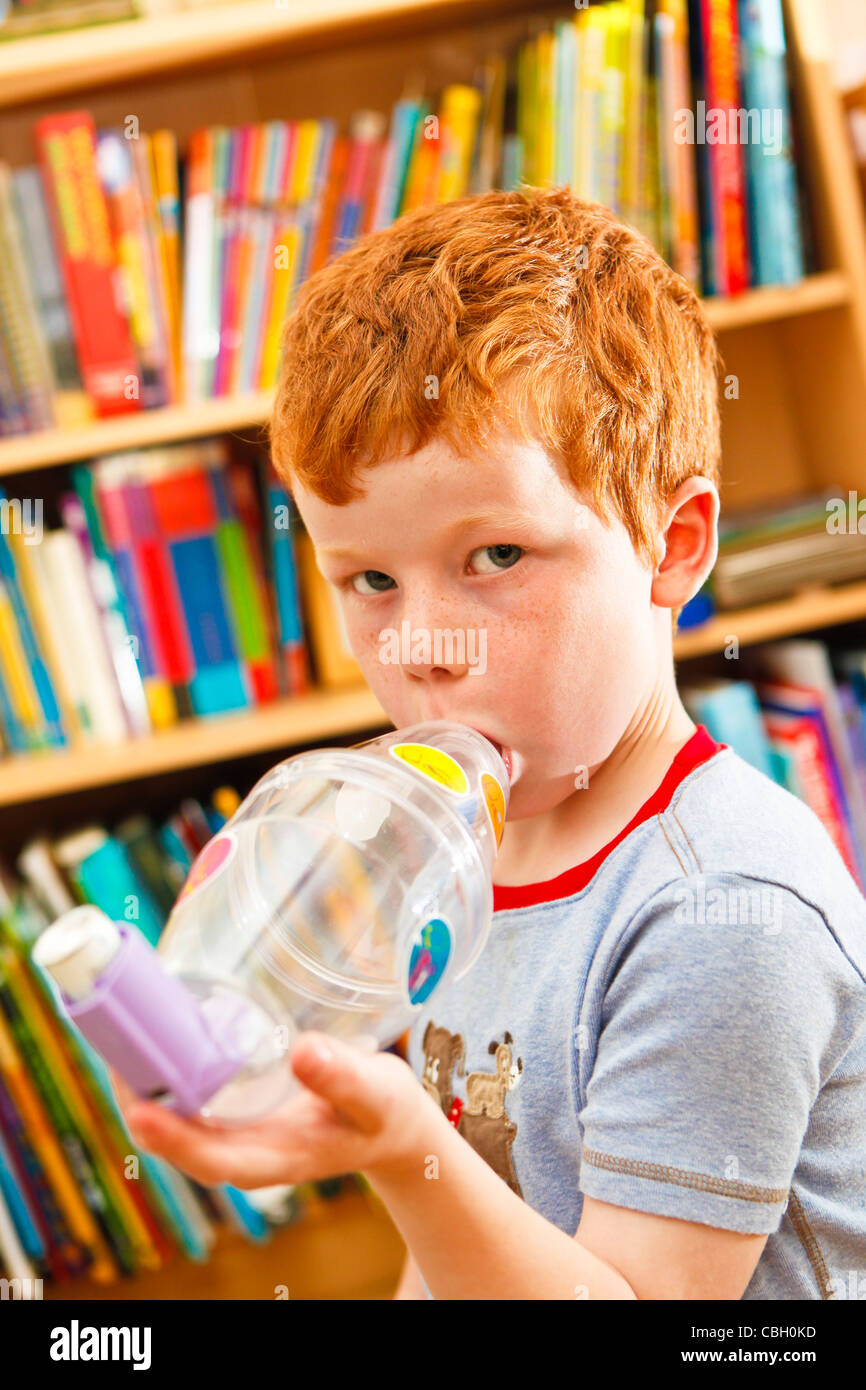 Young boy, aged 7, using an inhaler to combat asthma. Self medicating. - Stock Image