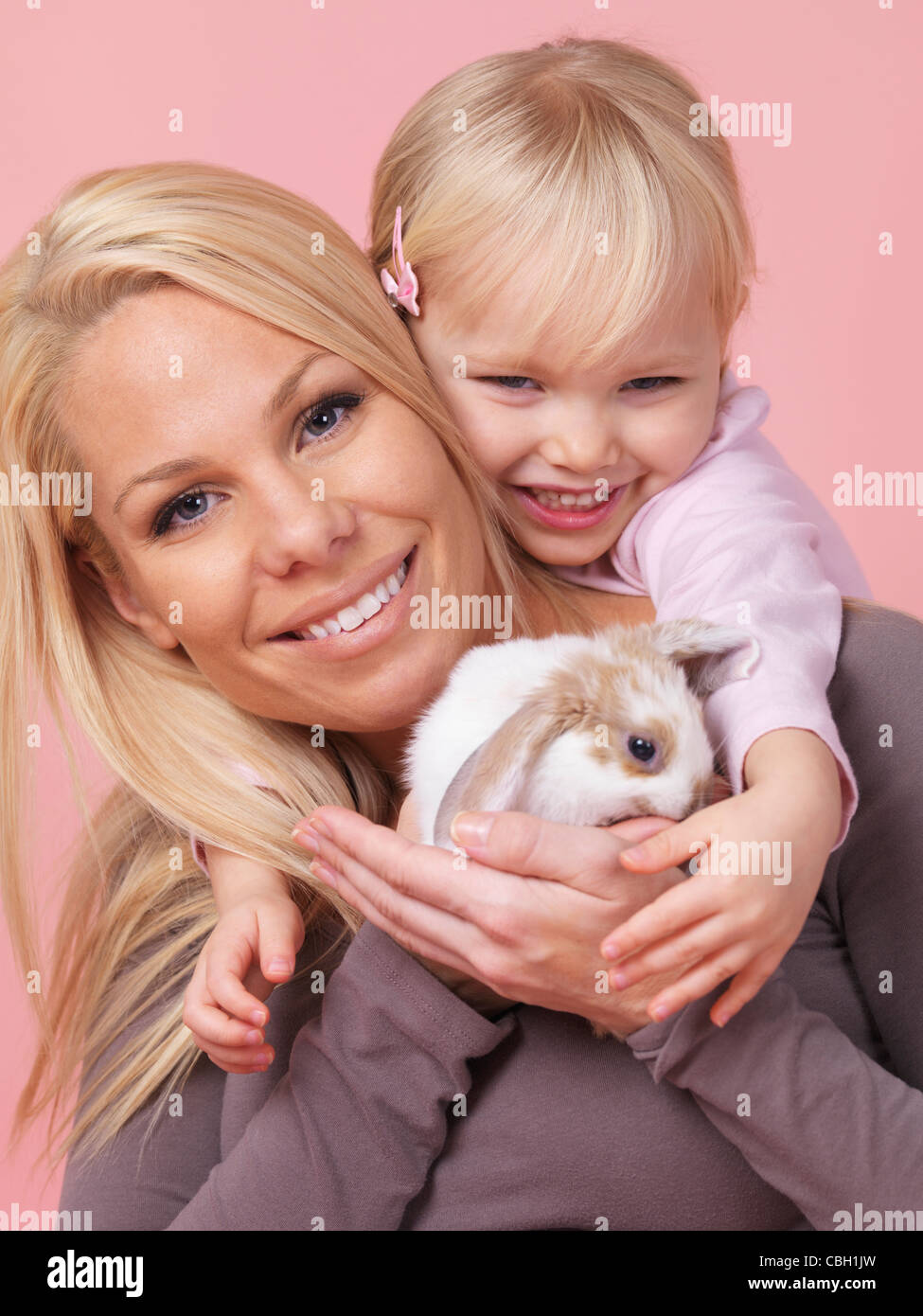 Portrait of a smiling three year old girl with her mother holding a pet rabbit in her hands isolated on pink background - Stock Image