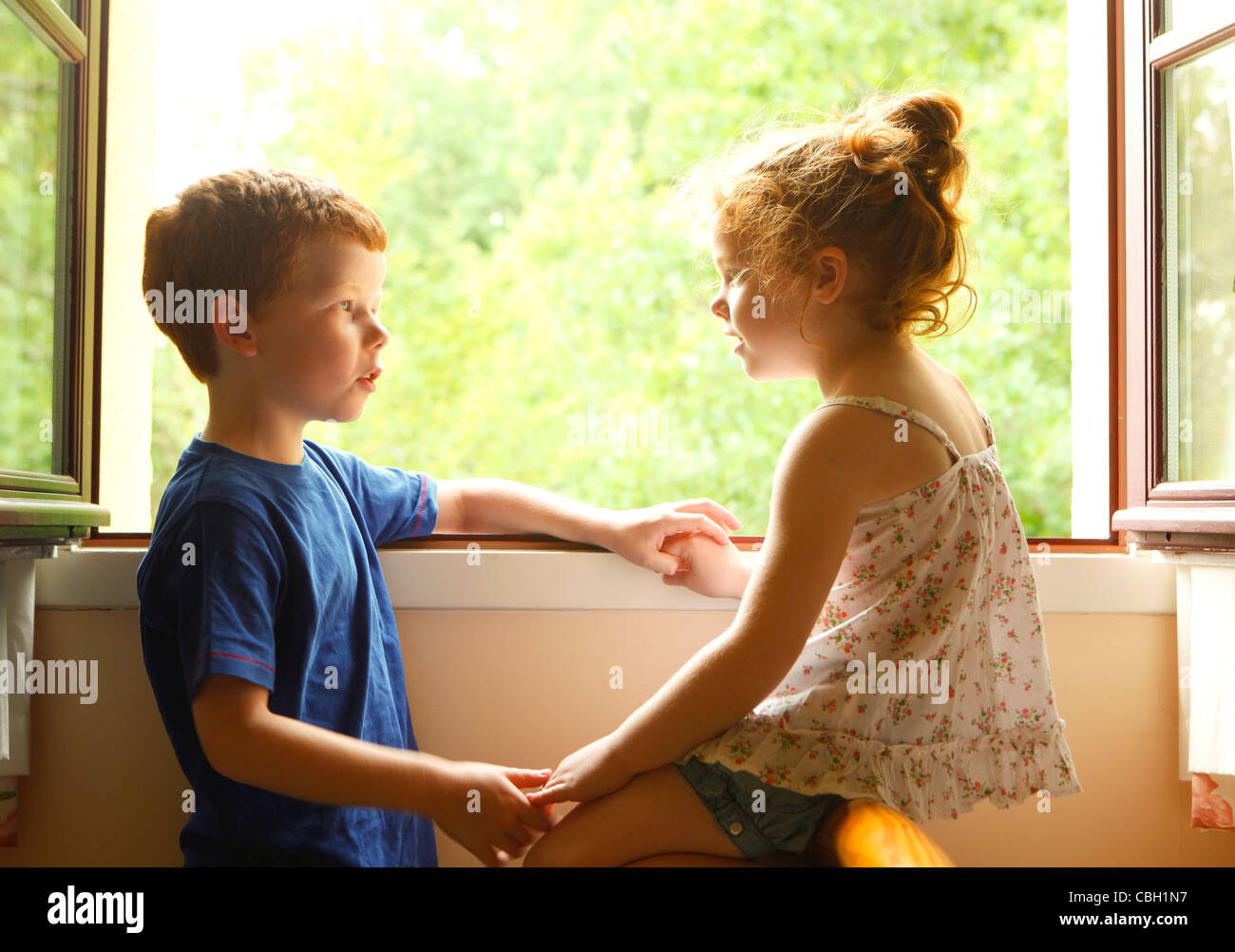 a brother and sister talking to each other by a window stock photo