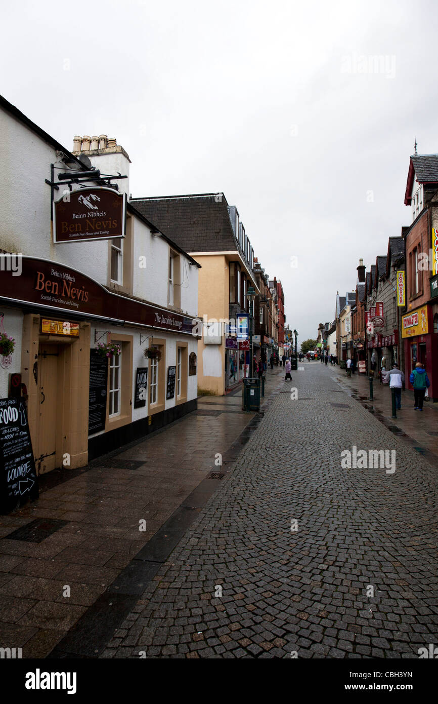 Main high street shopping street in Fort William, Scotland. pedestrianised road showing pubs and shops in the rain - Stock Image