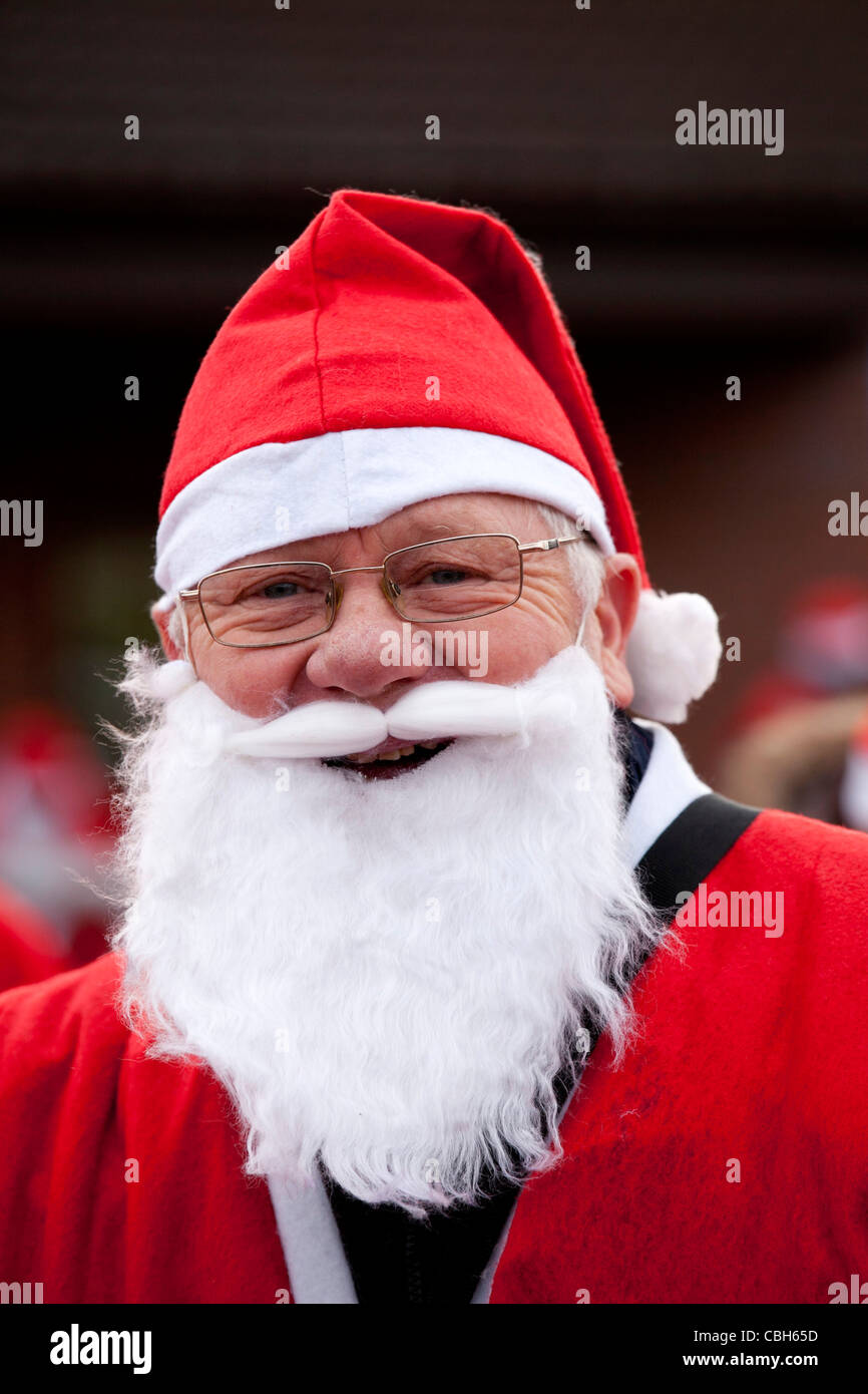 A person dressed in Santa costume taking part in a mile run to raise money for the Mary Evans Hospice in Nuneaton. - Stock Image