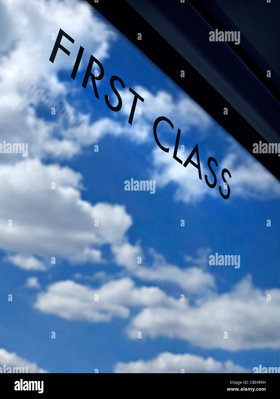 Concept ...First Class sign on window of railway carriage with infinity blue sky and clouds behind - Stock Image