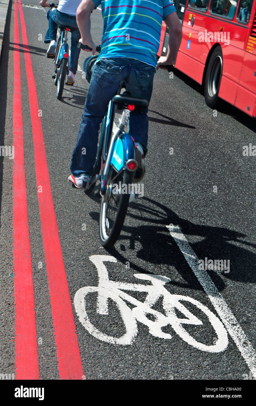Cyclists riding TFL hire bicycles crossing Westminster Bridge in bicycle lane Westminster London UK - Stock Image