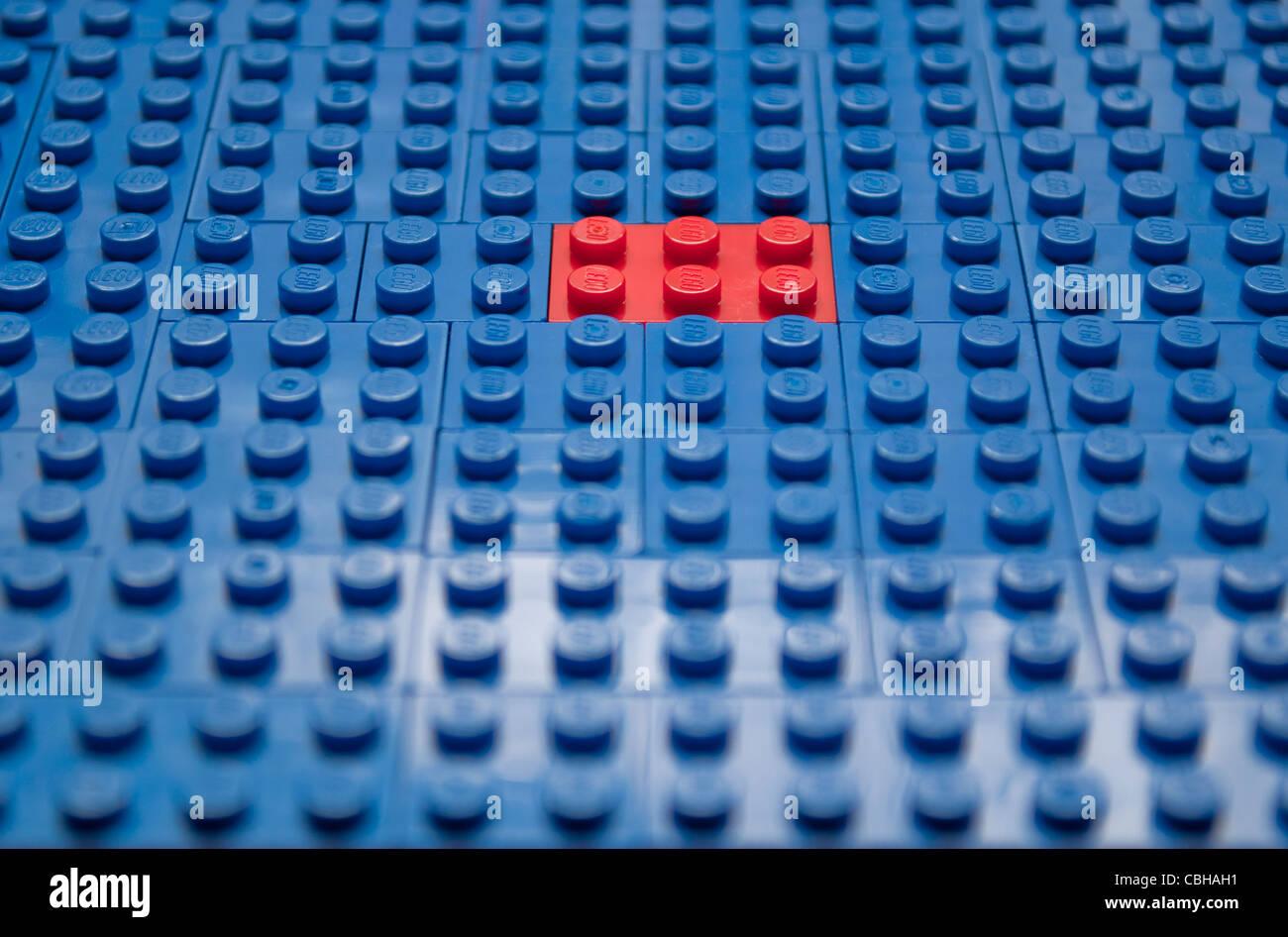 Bright red toy brick alone among bright blue bricks - Stock Image