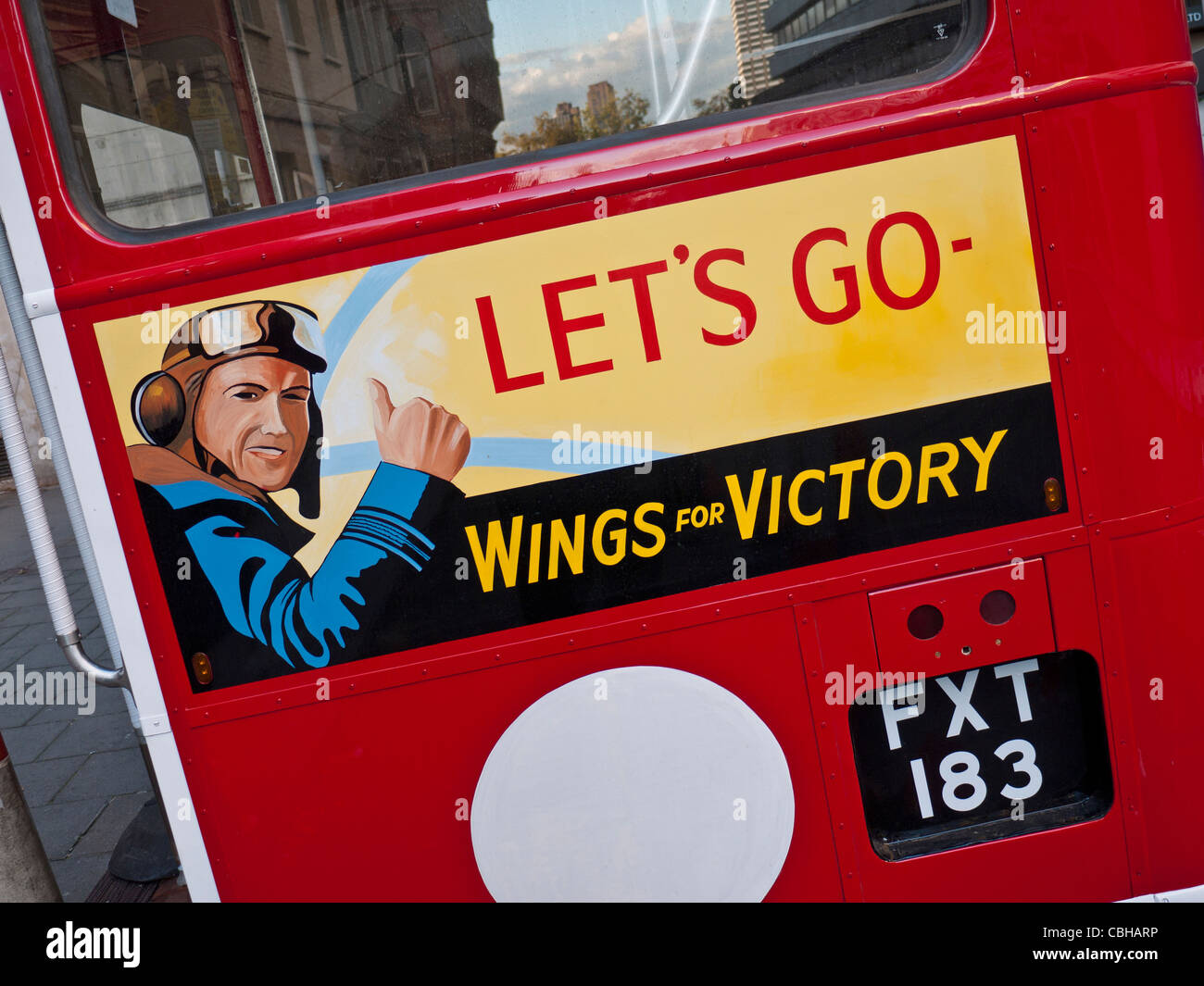 Historic 1940's restored traditional UK red double decker bus, with WW2 poster and slogan ' Wings for Victory' - Stock Image