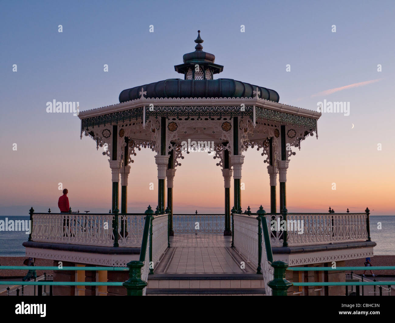 Victorian Bandstand on the promenade at sunset with lone figure enjoying the wide seascape view Brighton Sussex Stock Photo