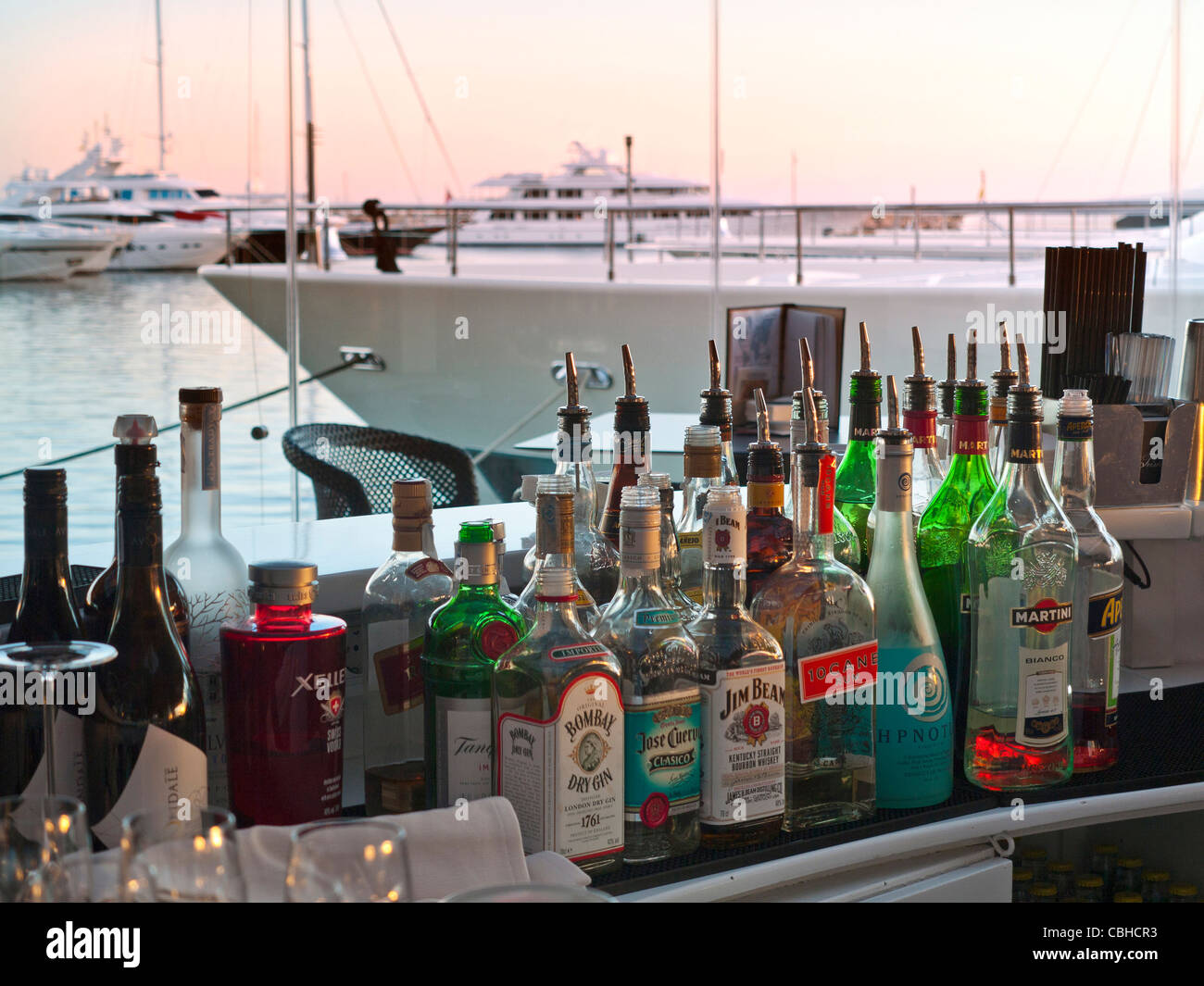 Variety of exotic alcoholic spirit bottles in chic waterside restaurant bar luxury marina resort Puerto Portals - Stock Image