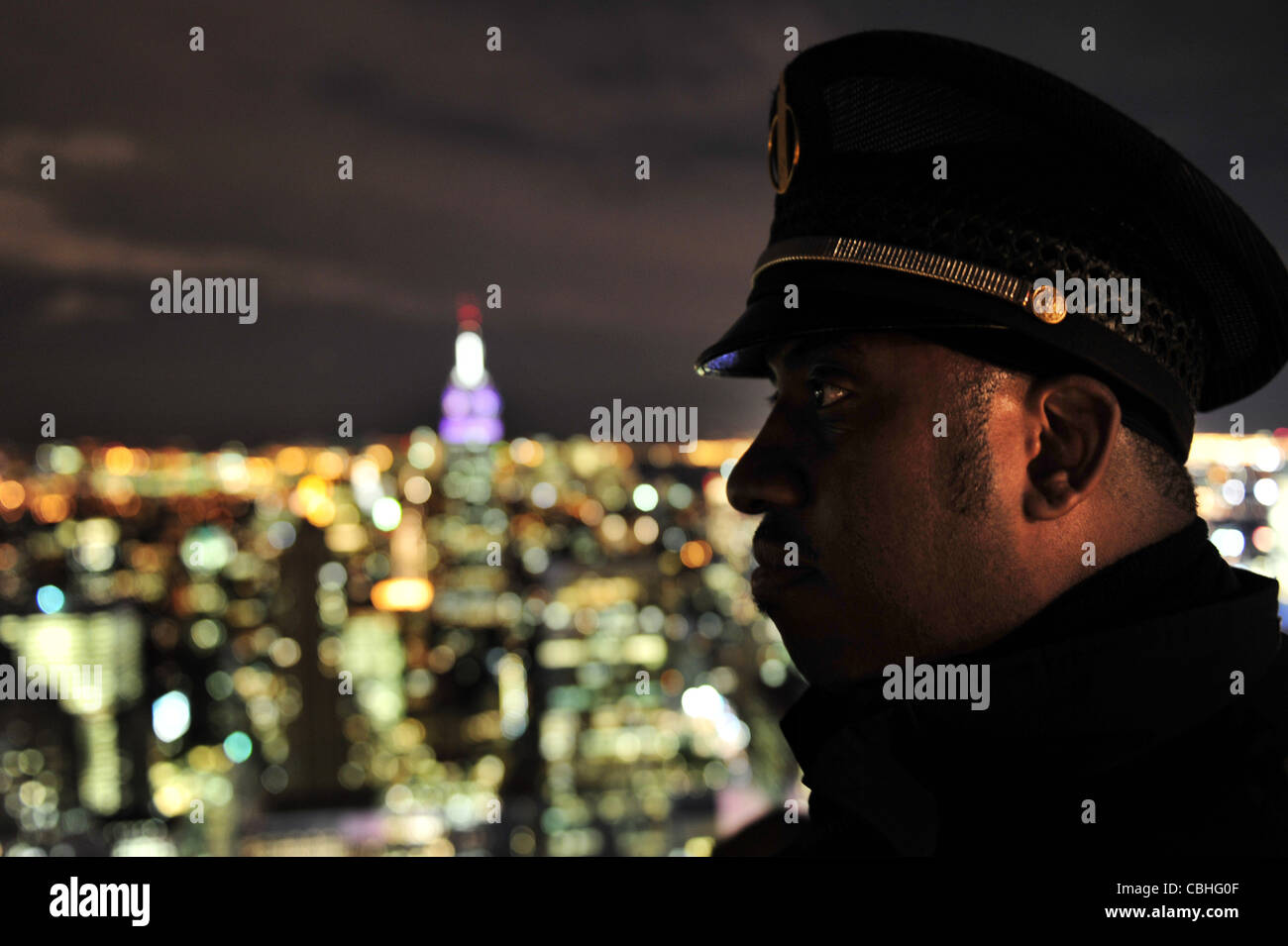 A security guard on looking at the Empire State Building Manhattan N.Y  New York at night - Stock Image