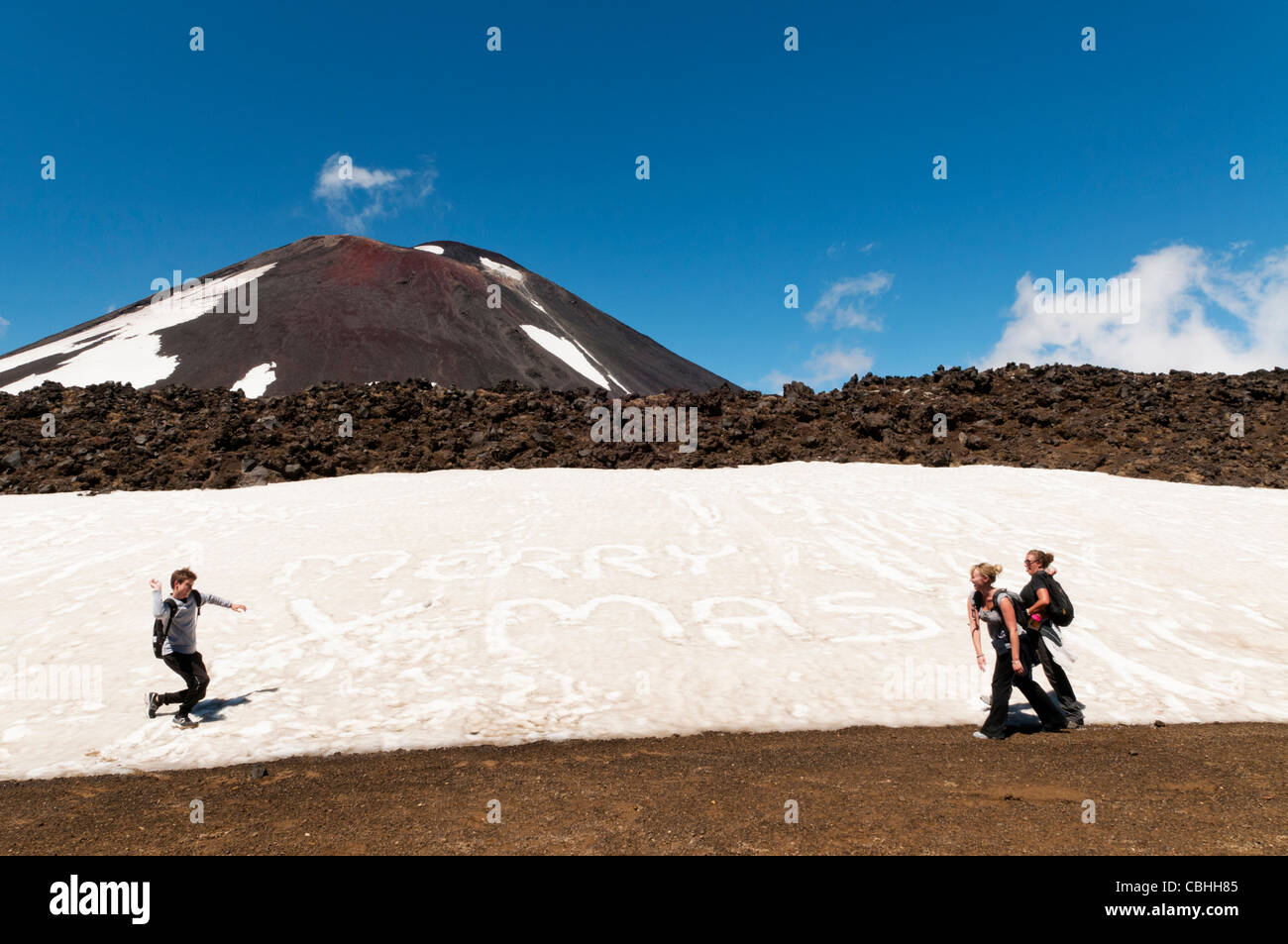 backpackers having a snow ball fight with merry christmas written in snow, in summeTongariro crossing National Park, - Stock Image