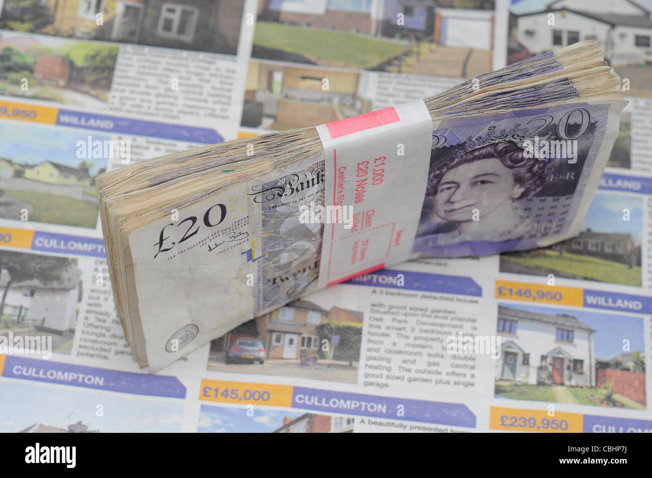 Property concept money on newspaper adverts homes for sale. £1000, monthly mortgage payments or saving for - Stock Image
