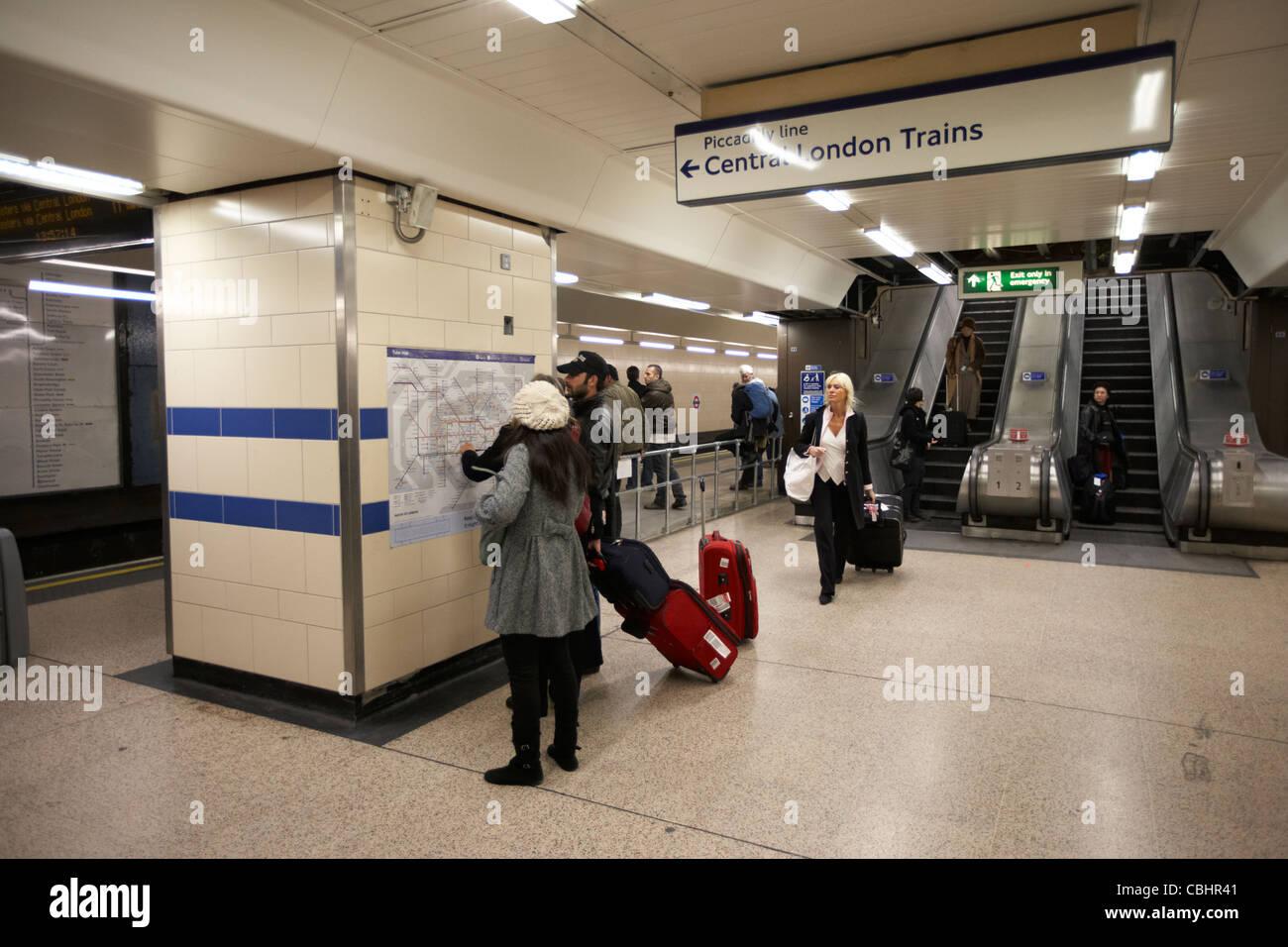 tourists consulting tube map at heathrow london underground station england united kingdom uk - Stock Image