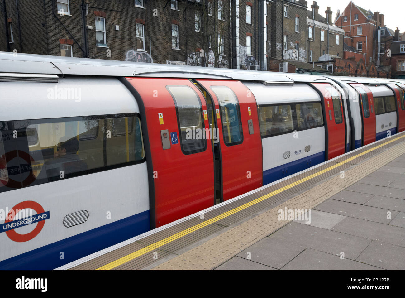 london underground train closing doors at outdoor above ground station england united kingdom uk - Stock Image