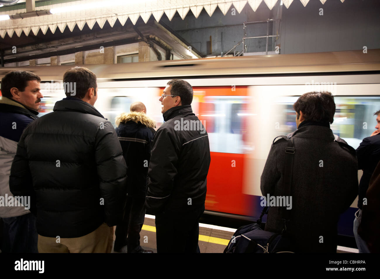 people standing on the platform as train speeds by london underground england united kingdom uk - Stock Image