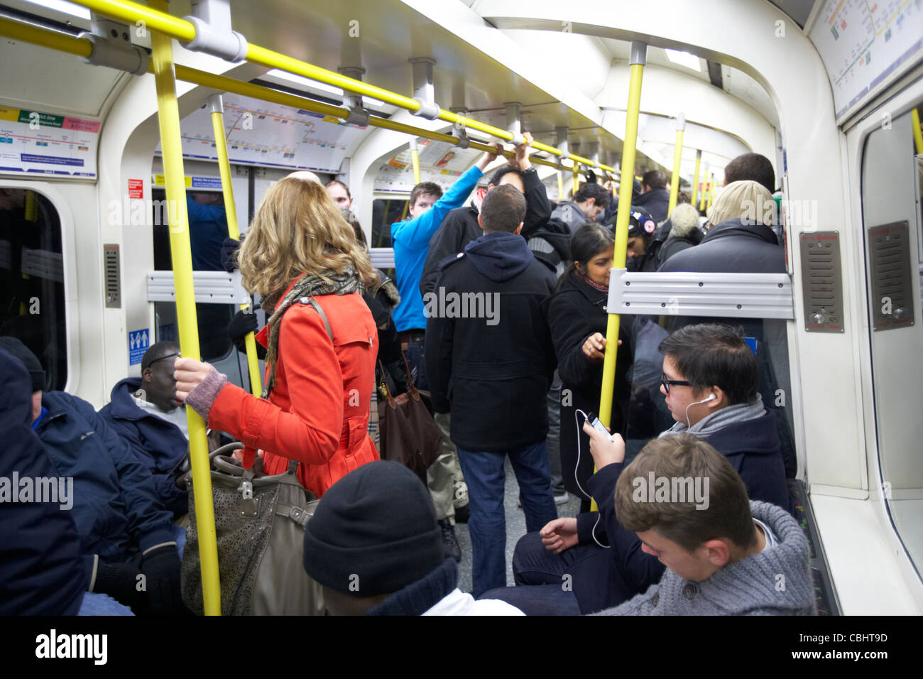 girl with red coat standing on busy tube train surrounded by people on london underground england united kingdom - Stock Image