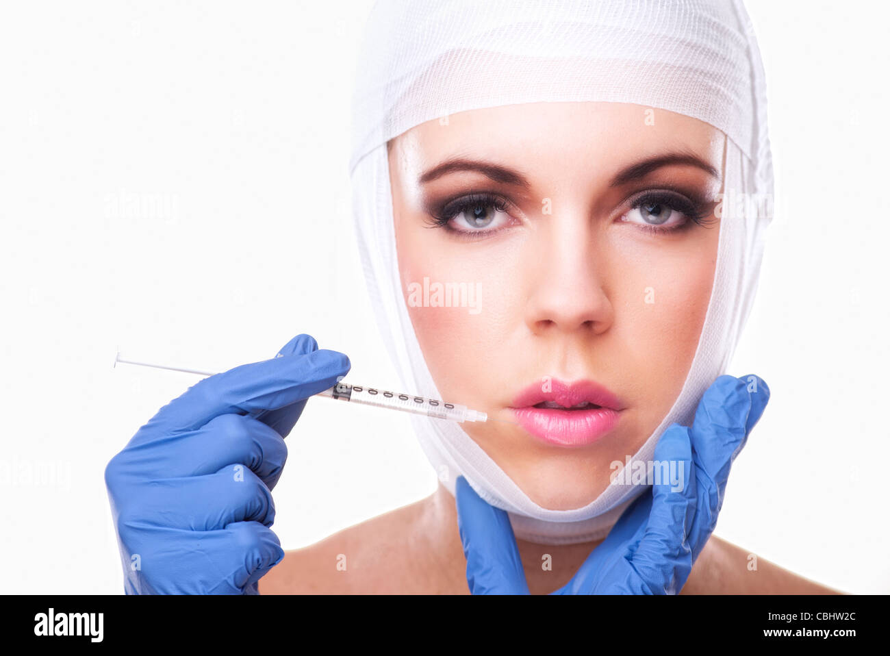 woman having lip plumping injection into lips - Stock Image